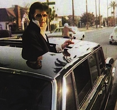 Elvis standing through the open sunroof of a '69 Mercedes 600 limousine he purchased in April, 1970 (Source: link)
